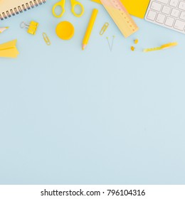 School or office background with stationery, notebook paper, keyboard, crayon, pen, ruller paper clip on blue and yellow colors. Flat lay.
