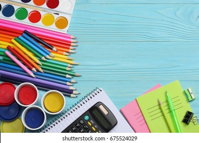 school and office supplies. school background. colored pencils, pen, pains, paper for  school and student education on blue wooden background. top view with copy space