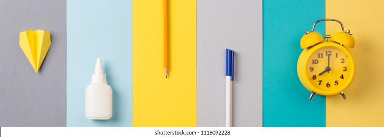 school and office supplies on bright striped background. minimum set in yellow, blue, gray color: pen, pencil, glue, alarm. concept: back to school, minimalism. Flat lay, top view, long banner