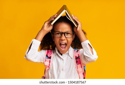 School Overload. Stressed African American Schoolgirl Screaming Angrily Covering Head With Book Over Yellow Studio Background.