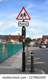School and school patrol warning traffic sign in a street in England.