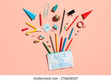 Schulstiftkoffer und Vorräte auf rosa Untergrund. Zurück zur Schule, Heimschule kreatives Bild.