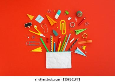 Schulbleistift und Vorräte auf rotem Tisch. Zurück zu abstraktem Schulhintergrund. Kreative Wohnung mit Kopienraum.