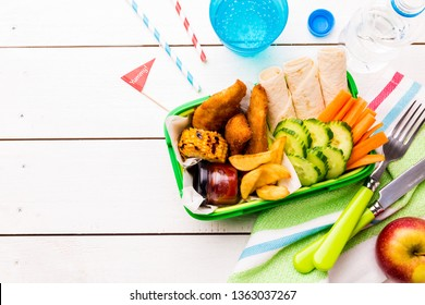 School or picnic lunch box with fried chicken strips, french fries, tortilla wraps and vegetables. White wooden table captured from above (top view, flat lay). Layout with free copy (text) space.