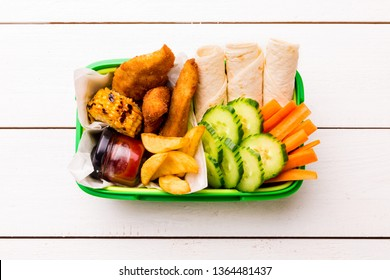 School or picnic lunch box with fried chicken strips, french fries, tortilla wraps and vegetables (carrot, corn, cucumber). White wooden table captured from above (top view, flat lay).