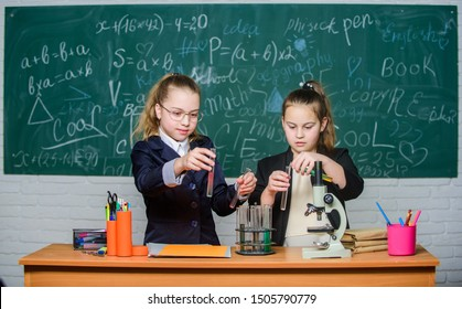 School project investigation. School experiment. Science concept. Gymnasium students with in depth study of natural sciences. Girls school uniform busy with proving their hypothesis. Private school.