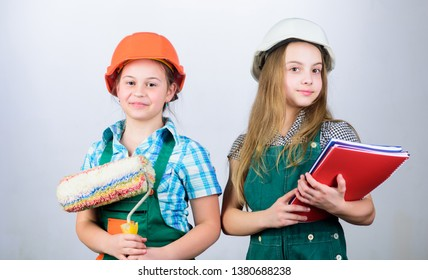 school project. small girls repairing together in workshop. Labor day. 1 may. Little kids in helmet with tablet and roller. Foreman inspector. Repair. i may is labor day. love working.