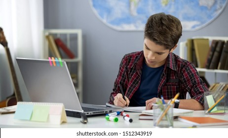 School pupil writing notebook doing home work at table, distance education