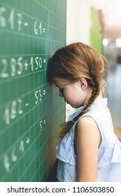 At school - Sad girl tries to count on the blackboard