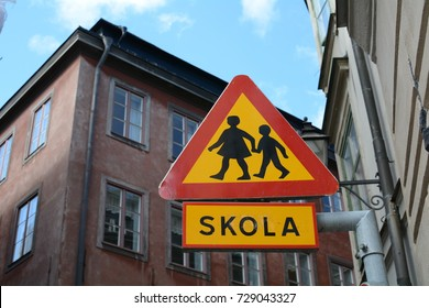 A school, or skola, sign in an old neighborhood of Stockholm, Sweden with old buildings in the background. - Shutterstock ID 729043327