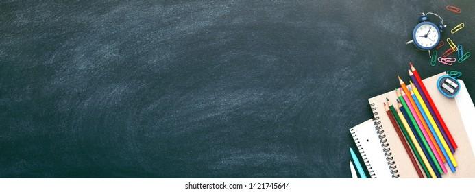 L'école était à l'arrêt sur le tableau. Ordinateurs portables, stylos, crayons, réveil, pomme rouge et autres outils. Bannière avec place pour texte.