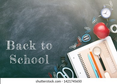School stationary on blackboard. Notebooks, pens, pencils, alarm clock, red apple and other tools. Flat lay with inscription Back to School.