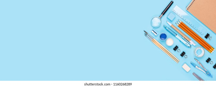 School stationary on blue background. Notebook, pens, pencils and other tools. Banner for site.