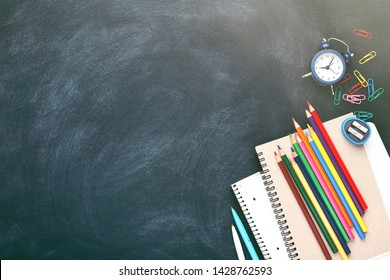 School stationary on chalkboard. Notebooks, pens, pencils, alarm clock and other tools. Flat lay with place for text.