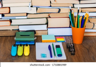 School stationery accessories - notebook, copybook stack with plastic holder pencils, pens, markers, paper clips, stickers, notepads, sharpener with stack of books education concept background