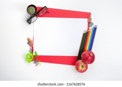 School stationery materials, glasses, apples and blank red paper on white office desk desk. Top view, flat lay with copy space