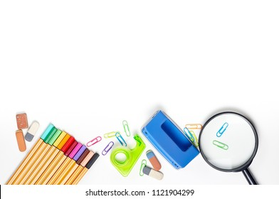 School stationery materials such as crayons, markers, clips, puncher, magnifying glass, erasers on white office table desk. Top view, flat lay with copy space