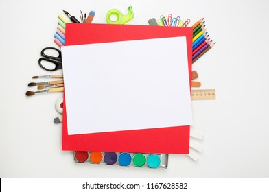 School stationery materials such as crayons, markers, watercolor paints and blank red paper sheet on white office table desk. Top view, flat lay with copy space