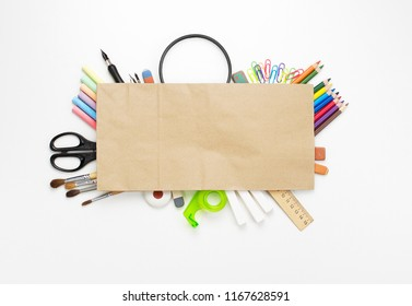 School stationery materials such as crayons, markers, magnifying glass and blank craft paper sheet on white office table desk. Top view, flat lay with copy space
