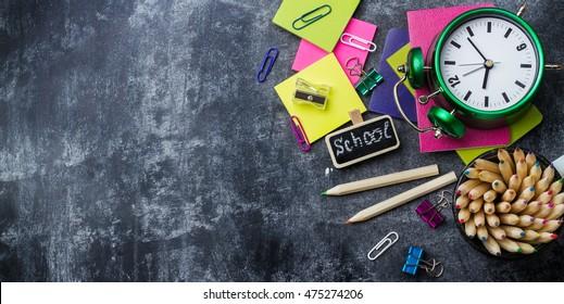 School stationery, pencil, pen, note, alarm clock on grunge chalkboard