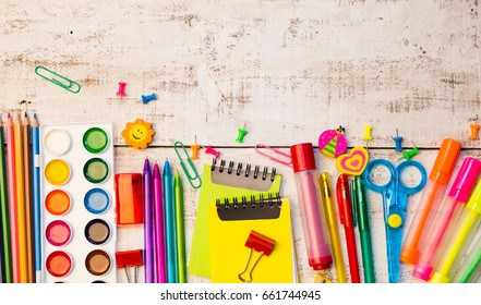 School stationery products such as paper clips, pins, notebooks, pens, pencils, rulers, scissors lying on white wooden table with space to write your text