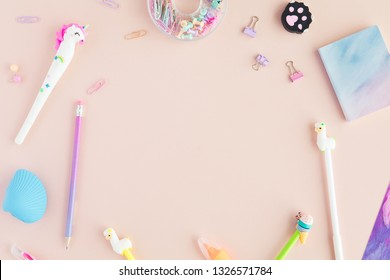 School stationery with unicorn pen, lama pencil on a pink background. Back to school creative table desk with kawaii stationery, flatlay and top view