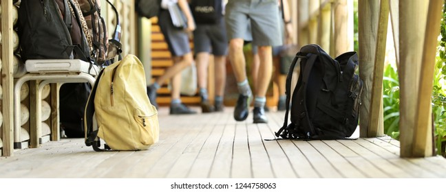 school student education concept. School bags outside a classroom with students in background. Blurred legs of students in uniform walking to class. Educational teacher school yard environment.