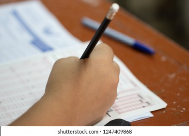 School Students hands taking exams, writing examination with holding pencil on optical form of standardized test with answers sheet on desk doing final exam in classroom. Education assessment Concept