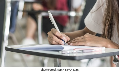 School student's taking exam writing answer in classroom for education test and literacy concept