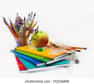 School subject to the Teacher Day (notebooks, pencils, compasses, rulers and green apple isolated on white background)