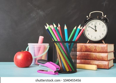 School supplies and alarm clock on table. Back to school concept.