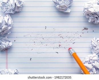 School supplies of blank lined notebook paper with eraser marks and erased pencil writing, surrounded by balled up paper and a pencil eraser. Studying or writing mistakes concept.