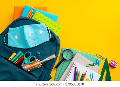 School supplies, blue backpack medical mask yellow background. Back to school, pandemic coronavirus concept, flat lay.Horizontal. Selective focus. View from above. Copy space.