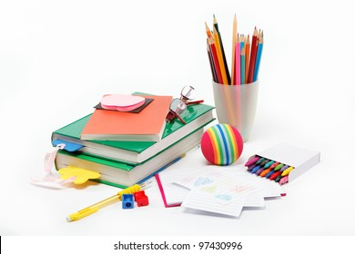 School supplies: books, notebook, pens, pencils, glasses, an apple on a white background.