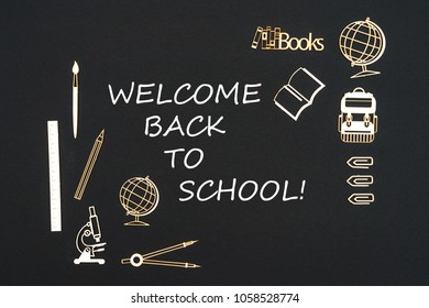 School supplies chipboard miniatures placed on blackboard with text welcome back to school. Concept back to school