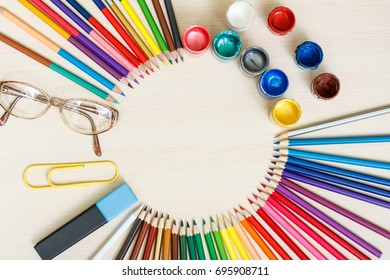 School supplies. Color pencils, glasses, big paper clip, marker and colorful paints in cups on wooden table. Top view. Back to school concept.