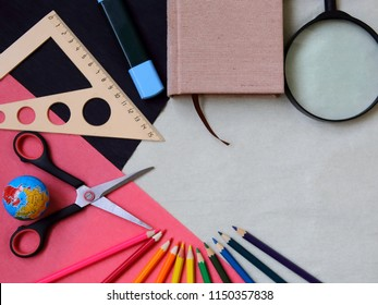School supplies, color pencils and yearbook on color pastel background