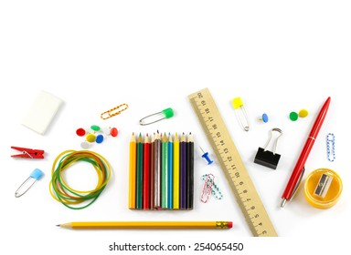 School supplies: colored pencils, wooden yardstick, erasers, binders, stationery gum, paper clips, pencil sharpener, a small clothespin, colored pins, pencil and pen isolated on white background