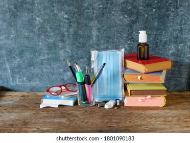School supplies and COVID 19 prevention items on classroom desk with books,eyeglasses,pens on chalkboard background. Back to school during corona-virus pandemic concept.