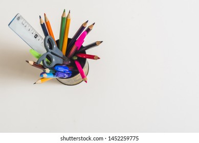 School supplies in cup on white background