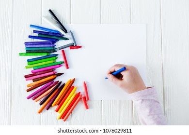 School supplies for drawing on the table: paper and crayons. A child is holding a crayon in his hands