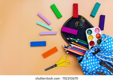 School supplies fall out of backpack on beige background. Top view.