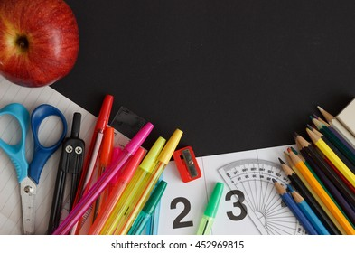 School supplies with fresh red apple on the blackboard with space for your text or graphic design.