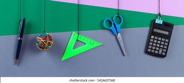 School supplies hang on the rope. School supplies on grey background. Back to school concept. banner