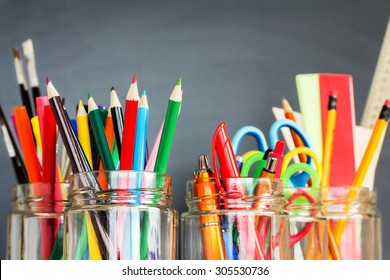 School supplies in jars against the blackboard
