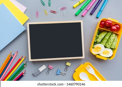 School supplies and lunch box with sandwich and vegetables. Back to school. Healthy eating habits concept - background layout with free text space. Flat lay composition, mockup, top view