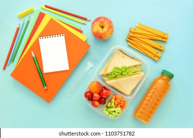 School supplies and lunch box with sandwiches, pieces of cucumbers and carrots, apricot, cherries, apple, bottle of juice on light blue background, back to school concept. Horizontal. Top view.