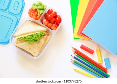 School supplies and lunch box with sandwiches, pieces of cucumbers and carrots, apricot, cherries, apple, bottle of juice on white background, back to school concept. Horizontal. Top view. Close-up,