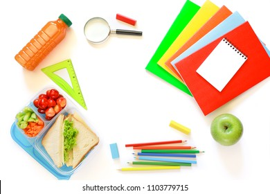School supplies, lunch box with sandwiches, pieces of cucumbers and carrots, apricot, cherries, apple, bottle of juice on white background, back to school concept with copyspace. Horizontal. Top view.