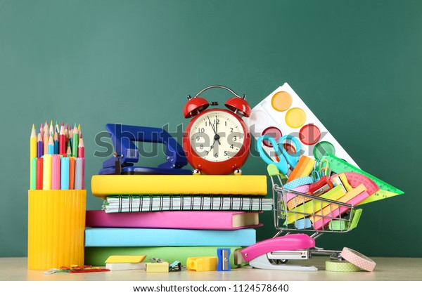 School supplies with notebook and books on chalkboard background